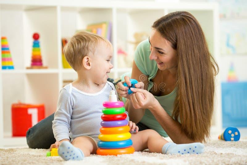 Leuk moeder en kindjongensspel samen binnen bij stock foto