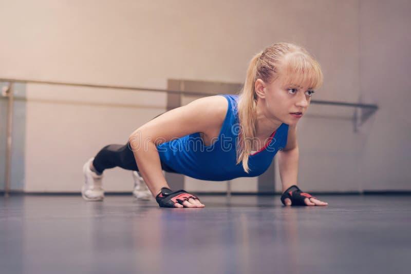 Leuk mooi blonde met blauwe ogen in blauwe sporten Jersey die oefeningen op de vloer doen Meisjesatleet die opdrukoefeningen doen royalty-vrije stock foto's