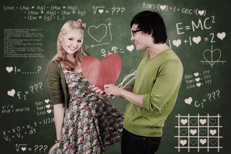 Leuk nerdkerel en meisje die liefde in klasse geven stock fotografie