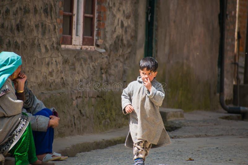Leuk onbezorgd dorpsjong geitje die traditionele kleding dragen die zijn neus plukken royalty-vrije stock afbeeldingen