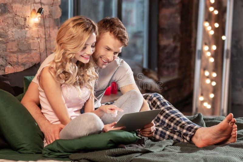Leuk paar die pyjama's dragen die rust in hun slaapkamer hebben stock foto's