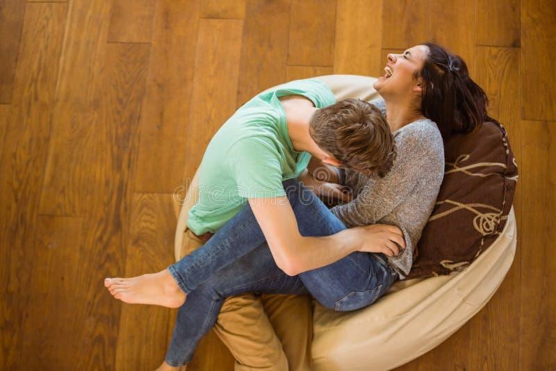Leuk paar die samen op beanbag lachen stock afbeeldingen