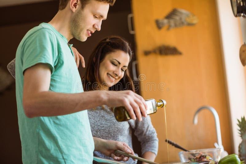 Leuk paar die voedsel samen voorbereiden stock foto's