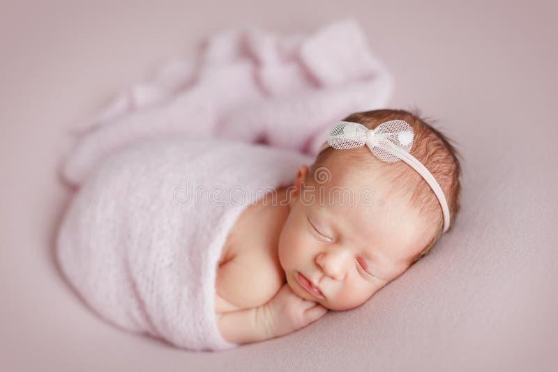 Leuk pasgeboren babymeisje met een boog op haar hoofdslaap op een roze stock foto
