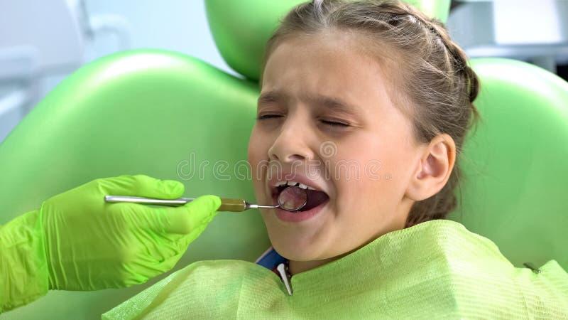Leuk peuterdiemeisje van tandcontrole met mondspiegel wordt doen schrikken, kinderachtige vrees stock foto's