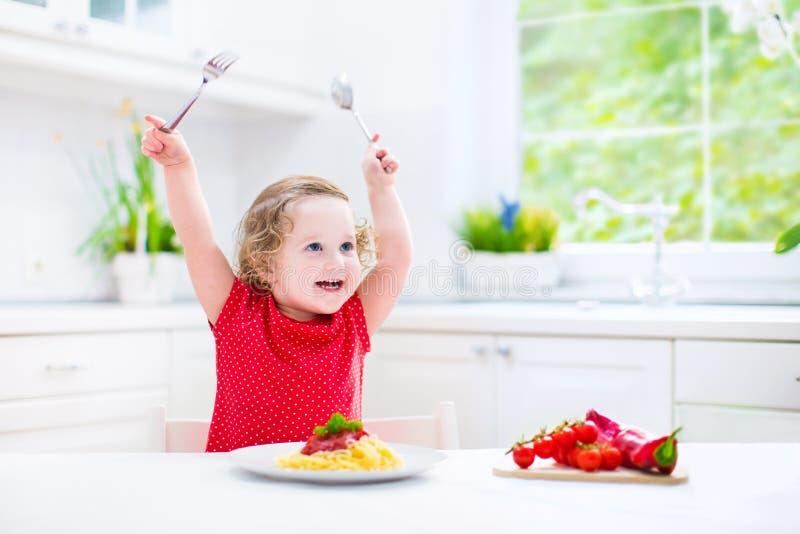Leuk peutermeisje die spaghetti in een witte keuken eten royalty-vrije stock afbeeldingen