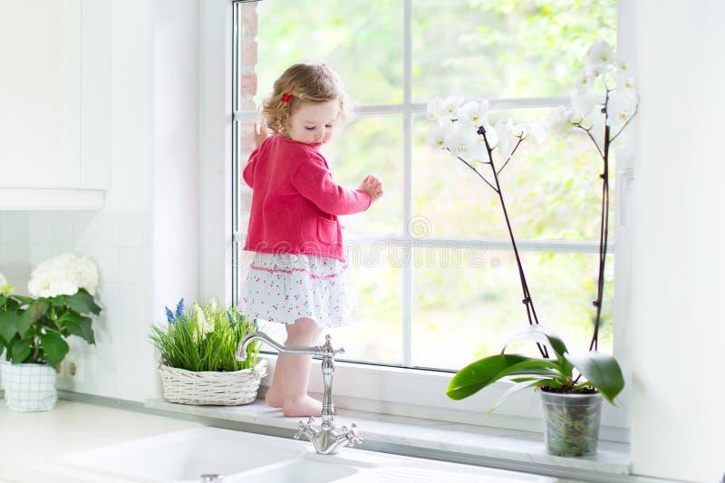 Leuk peutermeisje die venster in witte keuken opletten stock fotografie