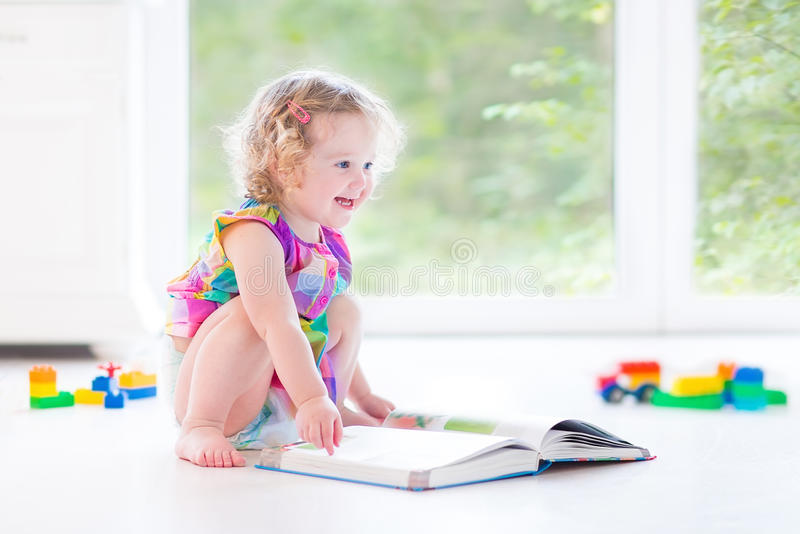 Leuk peutermeisje met het blonde krullende boek van de haarlezing royalty-vrije stock foto