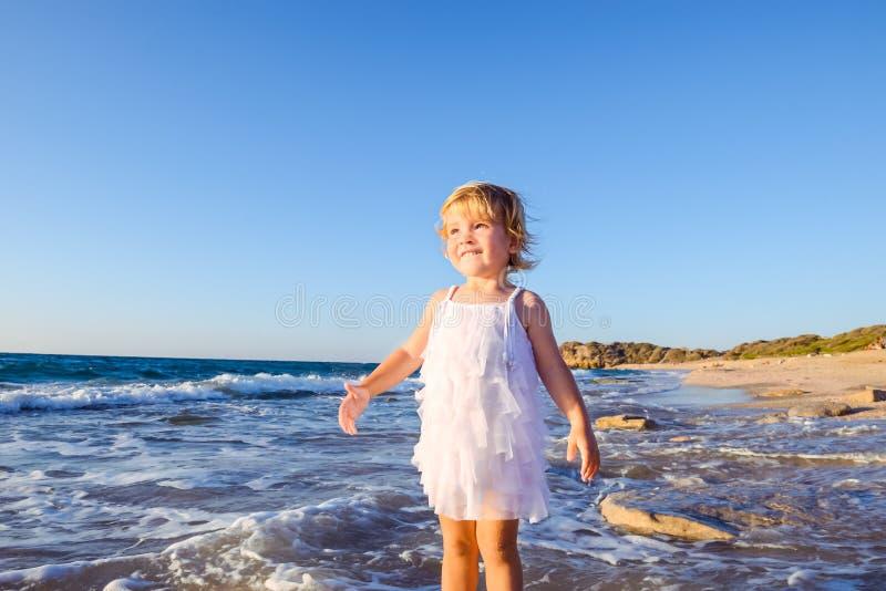 Leuk portret van weinig aanbiddelijk peutermeisje die in witte kleren op het lege strand op een warme zonnige de zomerdag lopen V stock afbeeldingen