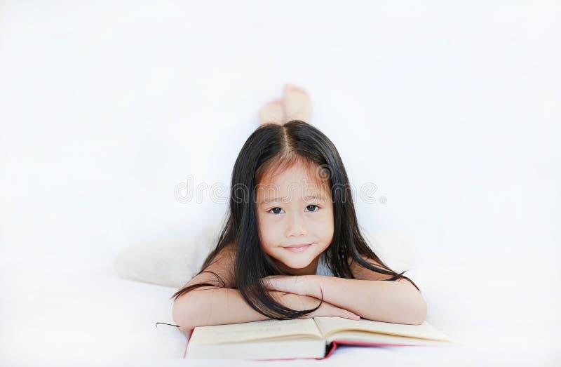 Leuk portret van weinig Aziatisch kindmeisje die een boek lezen die op witte achtergrond liggen royalty-vrije stock foto's