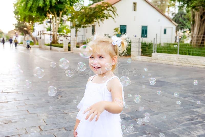 Leuk portret van weinig emotioneel blondy peutermeisje in witte kleding die en zeepbels spelen vangen tijdens gang in het stadspa royalty-vrije stock afbeeldingen