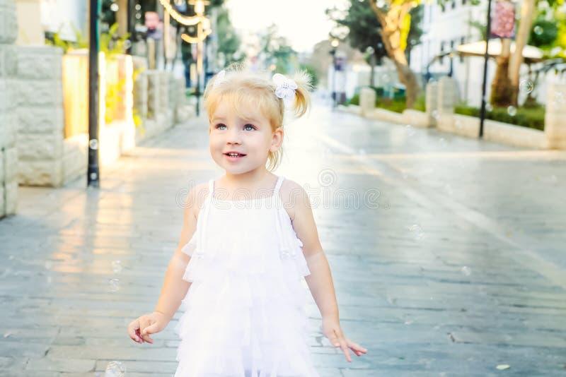 Leuk portret van weinig emotioneel blondy peutermeisje in witte kleding die en zeepbels spelen vangen tijdens gang in het stadspa stock afbeeldingen