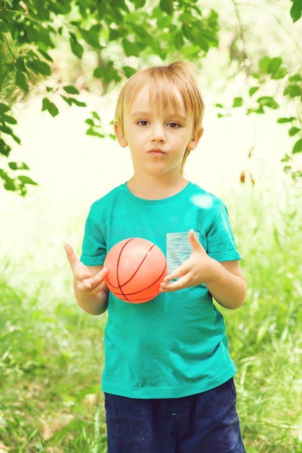Leuk portret van weinig jongen die met kleurrijke bal in tuin spelen Sport en vakantieconcept stock fotografie