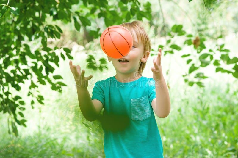 Leuk portret van weinig jongen die met kleurrijke bal in tuin spelen Sport en vakantieconcept stock afbeelding