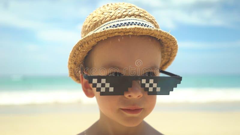 Leuk portret van weinig jongen in strohoed met zonnebril die zich op de zomerstrand bevinden royalty-vrije stock foto's