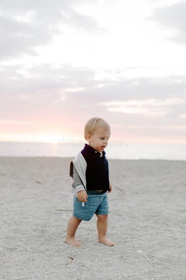 Leuk portret van Weinig Kind die van de Babyjongen en in het Zand bij het Strand tijdens Zonsondergang buiten op Vakantie in Hood royalty-vrije stock foto
