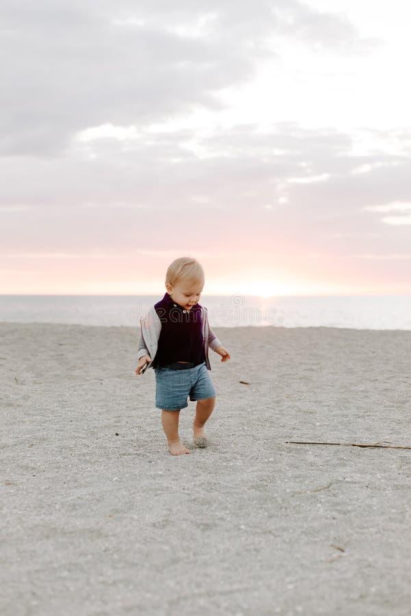 Leuk portret van Weinig Kind die van de Babyjongen en in het Zand bij het Strand tijdens Zonsondergang buiten op Vakantie in Hood royalty-vrije stock afbeeldingen