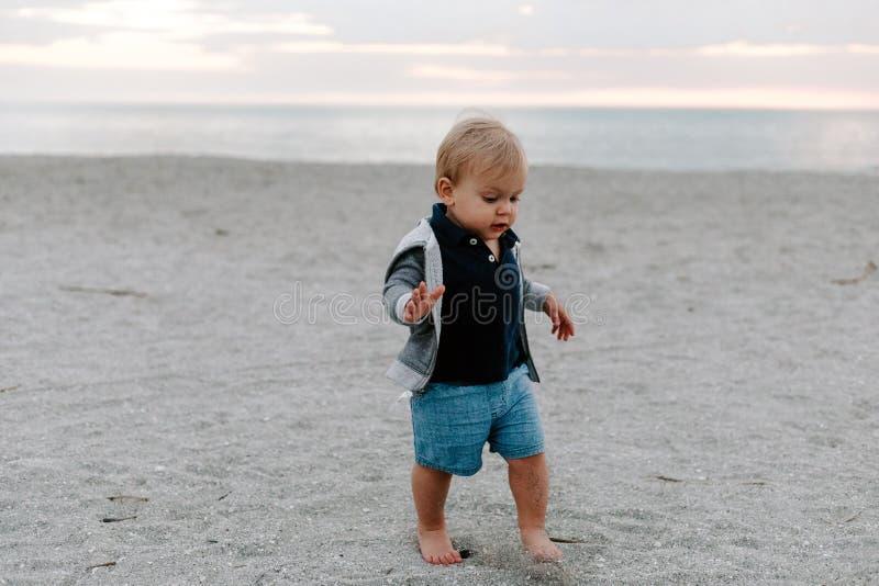 Leuk portret van Weinig Kind die van de Babyjongen en in het Zand bij het Strand tijdens Zonsondergang buiten op Vakantie in Hood stock afbeelding
