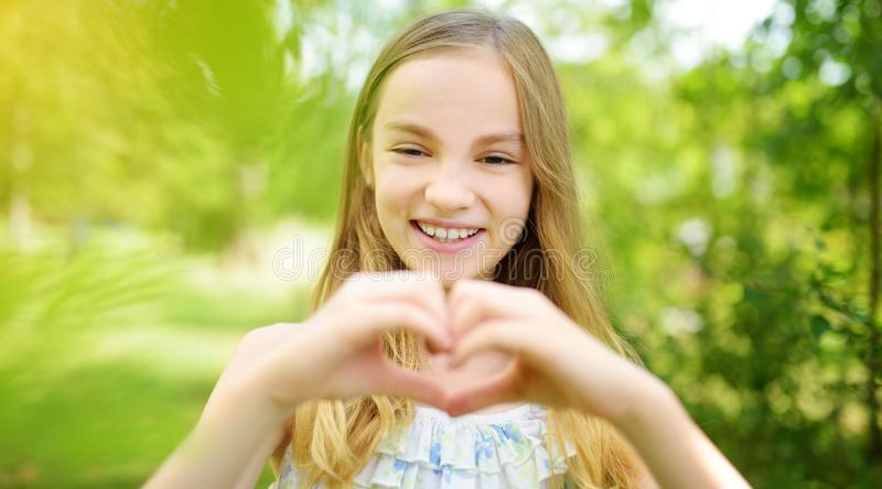 Leuk preteen meisje het lachen en het houden van haar dient een hartvorm op heldere en zonnige de zomerdag in Leuk kind die van g royalty-vrije stock foto
