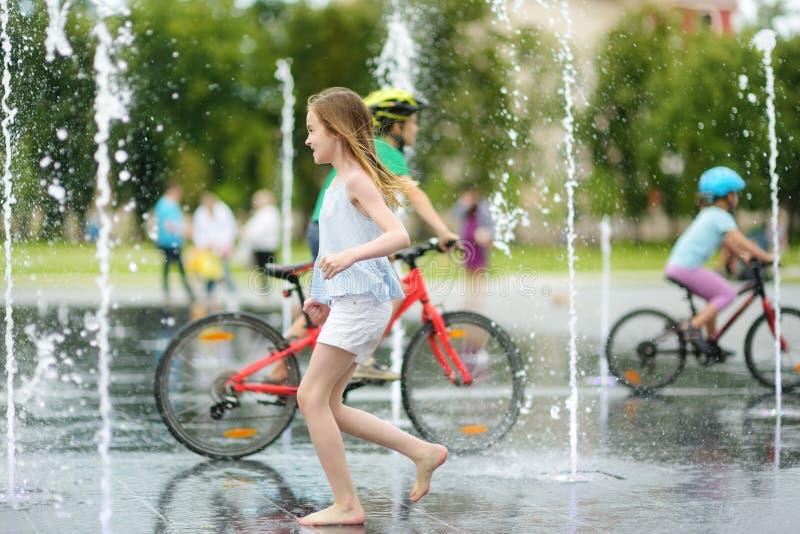 Leuk preteen meisje het spelen in fonteinen op onlangs vernieuwd Lukiskes-Vierkant in Vilnius, Litouwen Kind die pret met water h stock foto's