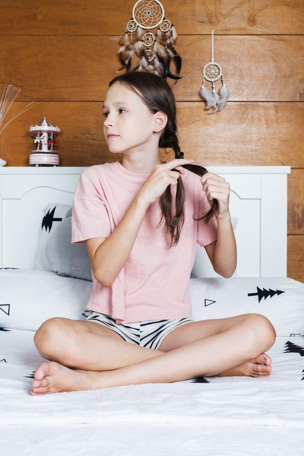 Leuk preteen meisje in roze t-shirt en de borrels vlechten haar haarzitting op bed in de ruimte van de bohostijl met houten muur  royalty-vrije stock fotografie