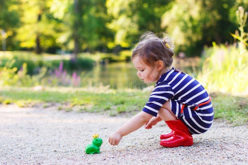 Leuk prinsesmeisje dat in rode regenlaarzen met rubberstuk speelgoed speelt voor stock foto