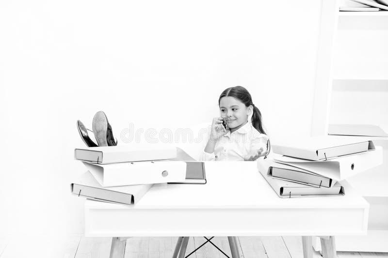 Leuk roddelmeisje Schoolmeisje het glimlachen het gezicht bespreekt verse roddels met partners Mobiele smartphone van het kindgeb royalty-vrije stock foto's