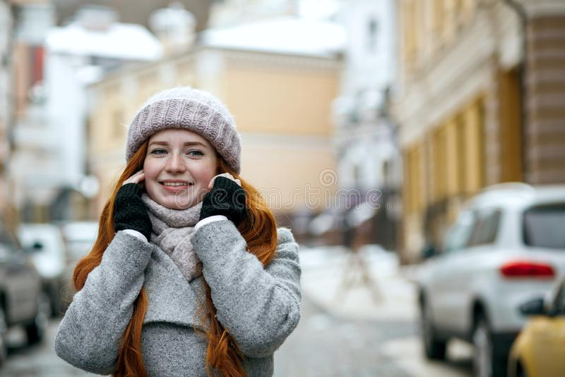 Leuk rood haired meisje die warme de winterkleren dragen die onderaan Th lopen stock foto
