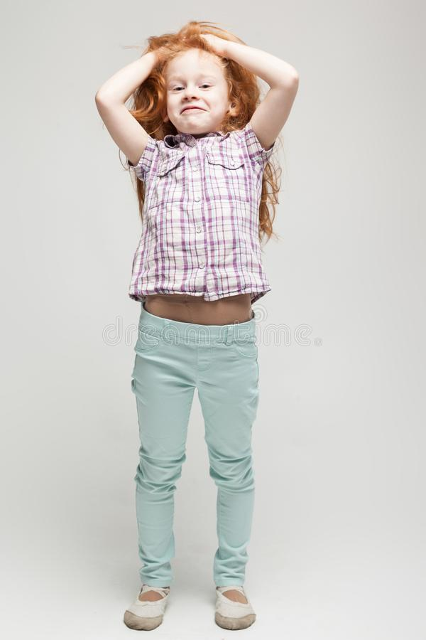 Leuk roodharigemeisje in plaidoverhemd, heldere blauwe broeken en witte laarzen stock fotografie