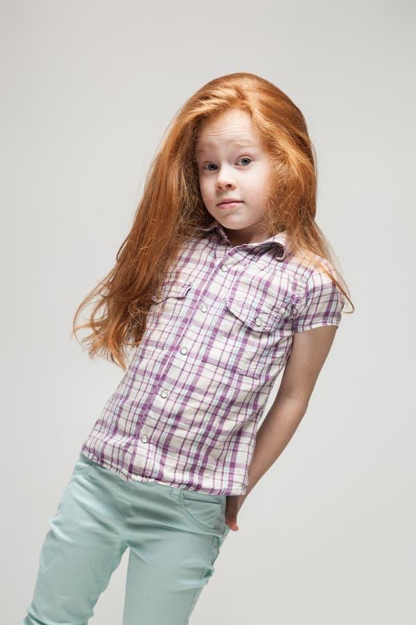 Leuk roodharigemeisje in plaidoverhemd, heldere blauwe broeken en witte laarzen stock afbeelding