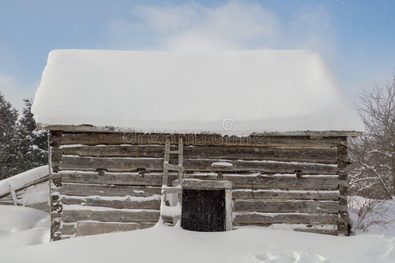 Leuk rustiek blokhuis in de sneeuw met meer vlokken het vallen en B stock fotografie