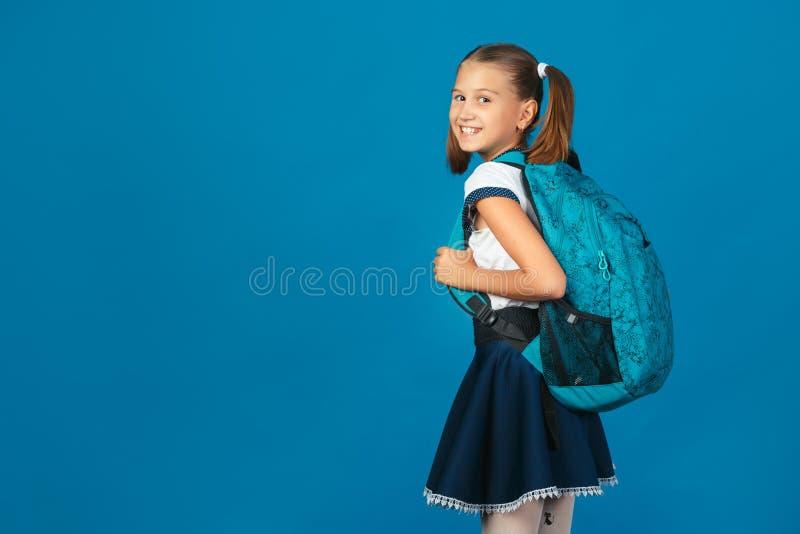 Leuk schoolmeisje die met blauwe rugzak camera op blauwe achtergrond bekijken royalty-vrije stock fotografie