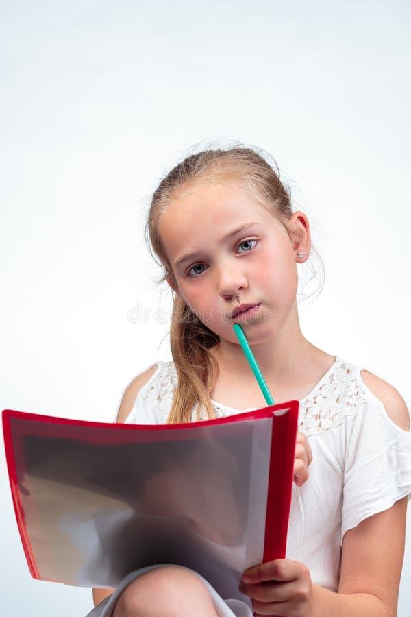 Leuk schoolmeisje die ongerust gemaakt een gat makend in potlood tegen kin kijken royalty-vrije stock foto's