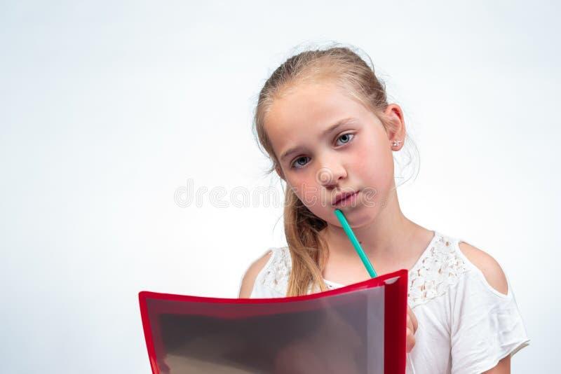 Leuk schoolmeisje die ongerust gemaakt een gat makend in potlood tegen kin kijken royalty-vrije stock foto
