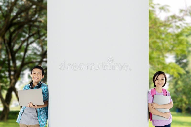 Leuk schoolmeisje die op een muur met haar broer leunen royalty-vrije stock afbeelding