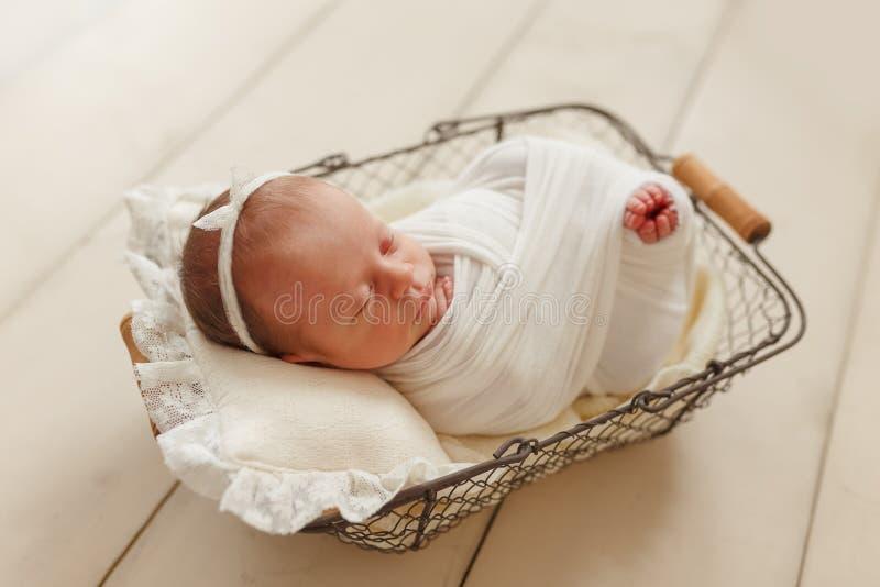 Leuk slaap pasgeboren meisje met een verband op haar hoofd op klein stock afbeelding