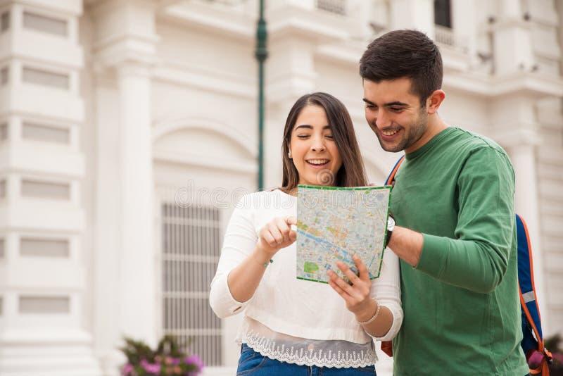 Leuk Spaans paar die een kaart lezen stock fotografie