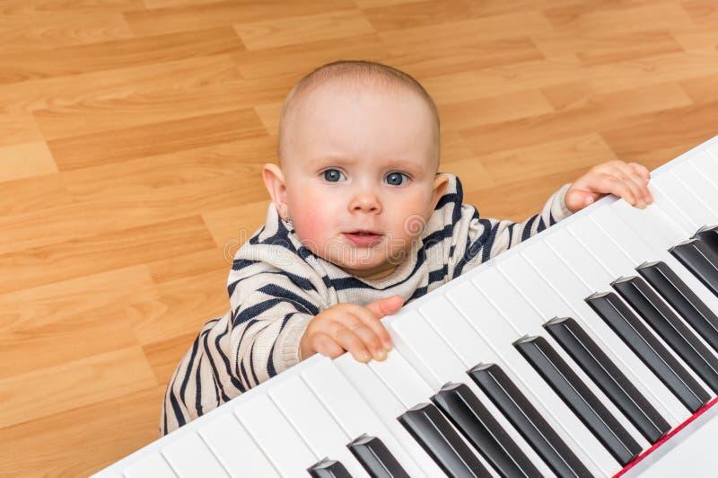 Leuk speelt weinig baby piano stock fotografie
