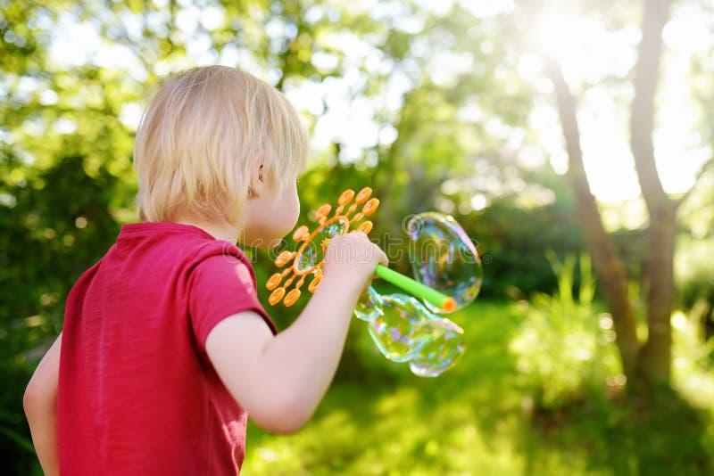 Leuk speelt weinig jongen met grote bellen openlucht Het kind blaast gelijktijdig grote en kleine bellen royalty-vrije stock afbeelding