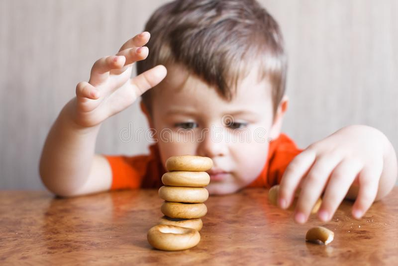 Leuk speelt weinig jongen met Ongezuurd broodje royalty-vrije stock afbeelding