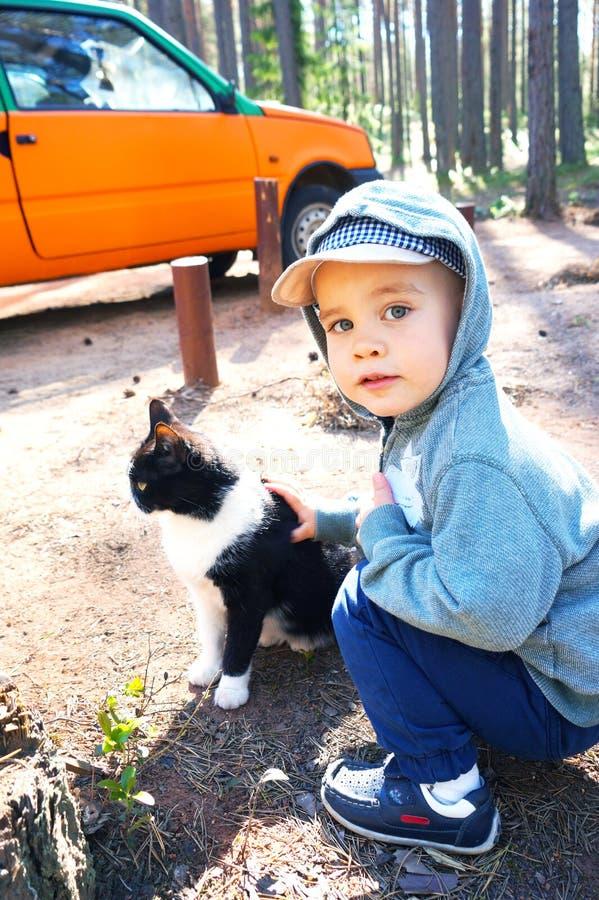 Leuk speelt weinig jongen met zwart-wit katje, strijkt het tegen de achtergrond van een oranje auto royalty-vrije stock afbeeldingen