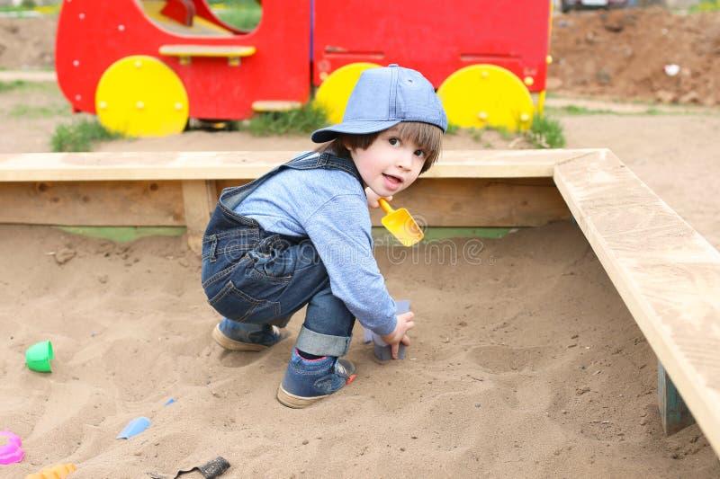 Leuk speelt weinig jongen in sandpit stock fotografie