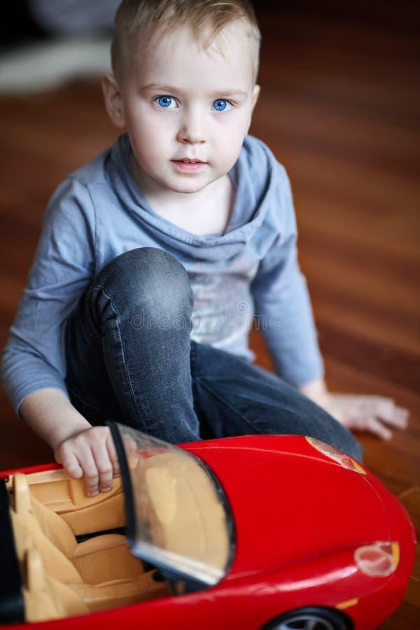 Leuk speelt weinig Kaukasische jongen, blond met blauwe ogen, met een stuk speelgoed - rode auto, zittend op de vloer Mooi Kind stock foto