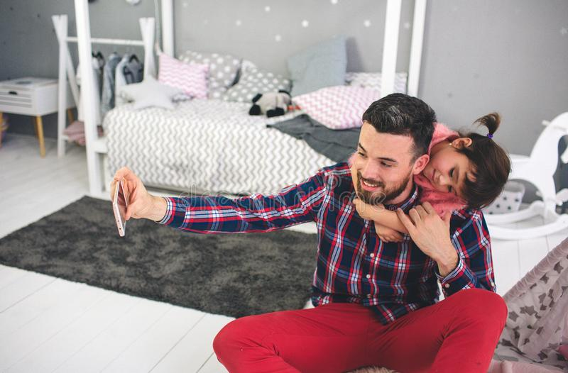Leuk spelen weinig dochter en haar knappe jonge papa samen in kind` s ruimte De papa en het kind brengen tijd door royalty-vrije stock foto's