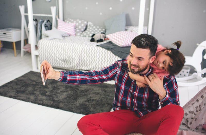 Leuk spelen weinig dochter en haar knappe jonge papa samen in kind` s ruimte De papa en het kind brengen tijd door stock afbeeldingen