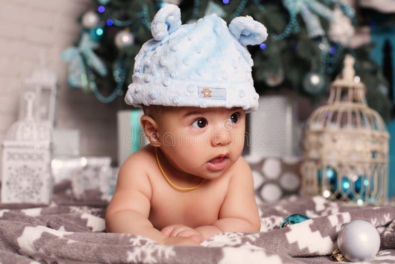 Leuk stelt weinig baby die naast Kerstboom met heel wat liggen voor stock foto's