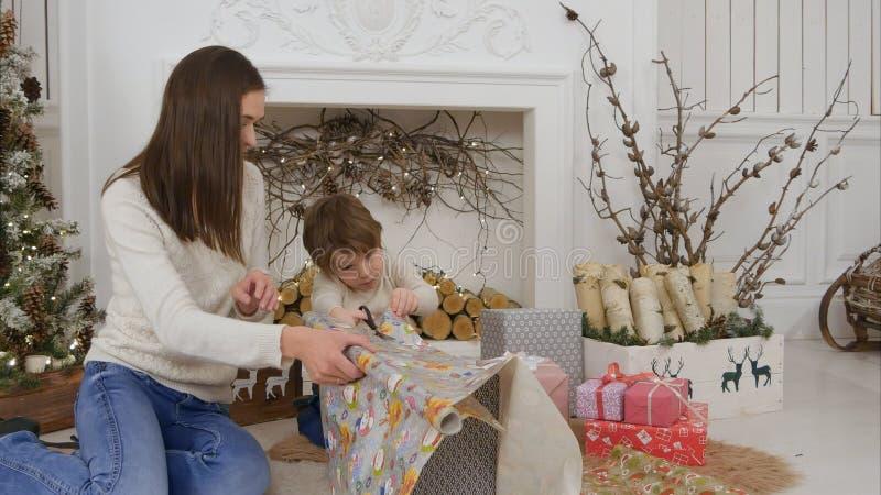 Leuk stelt weinig jongen die zijn moeder helpen om document te snijden voor omhoog het verpakken van Kerstmis voor royalty-vrije stock afbeelding