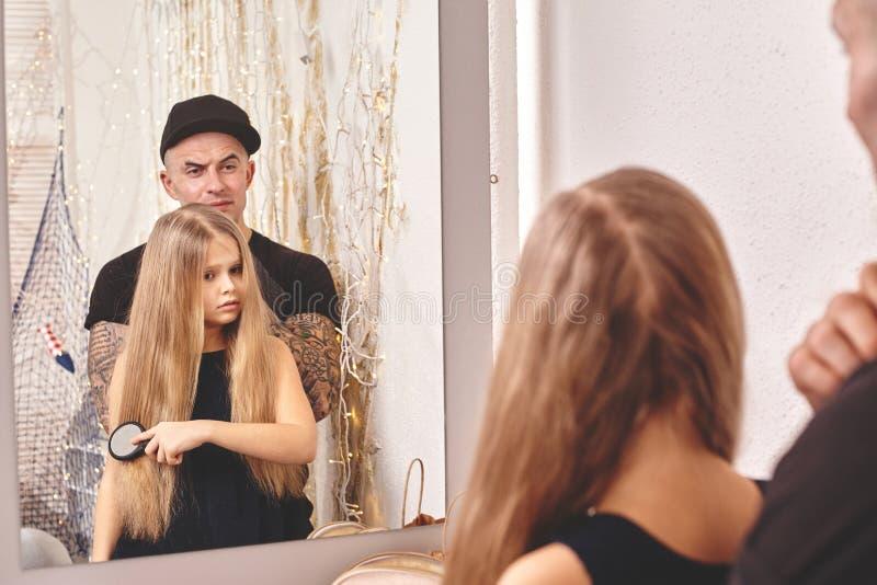 Leuk tattoed weinig dochter en haar papa spelen samen dichtbij een spiegel De papa doet het haar van zijn dochter Familie stock foto