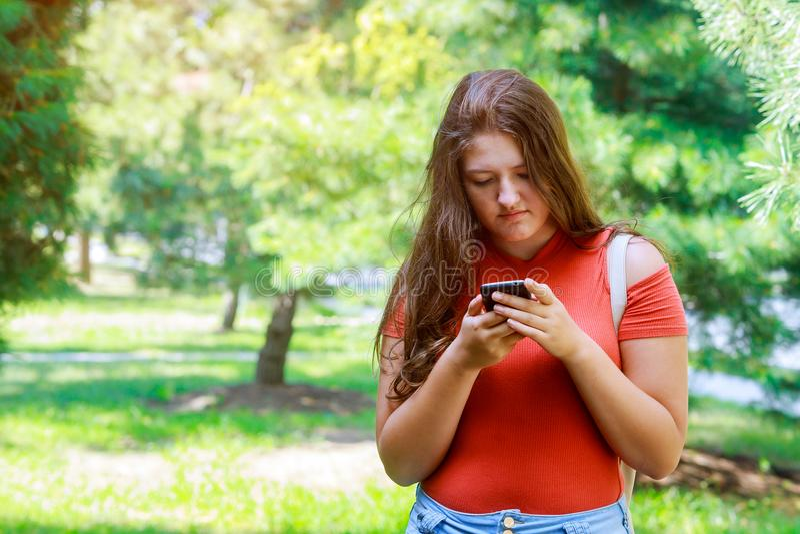 Leuk tienermeisje die een slimme telefoon in een park met een groene achtergrond met behulp van royalty-vrije stock foto's