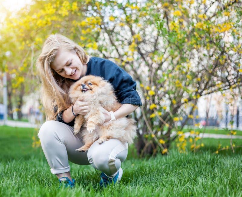 Leuk tienermeisje met het blonde haar spelen met haar Pomeranian-puppy stock afbeelding